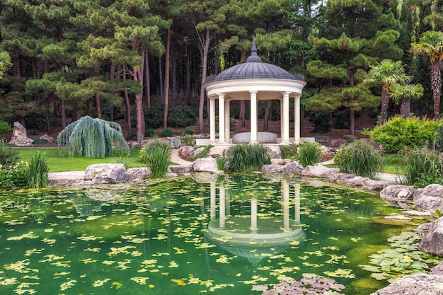 White pavilion near the green pond in the garden with reflection in the summer day. alcove architecture in coniferous forest.