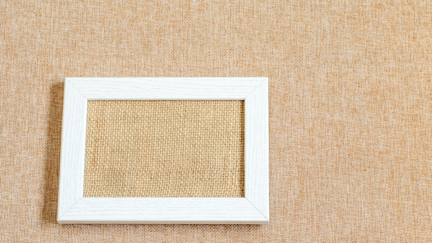 White pciture frame blank on the eco friendly textured burlap fabric. mock up photo.