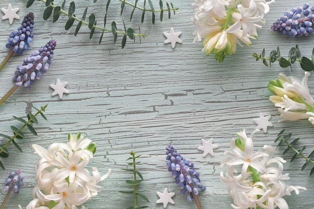 White pearl and blue grape hyacinth flowers with eucaliptus plants on light rustic textured wood