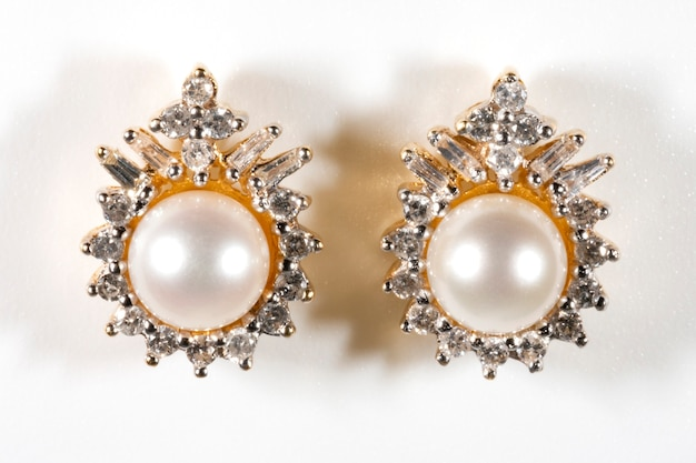 White pearl earring with prong studded diamond halo earring in yellow gold