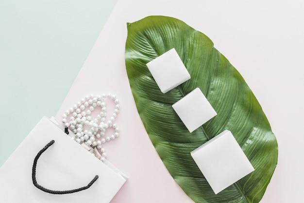 Белое жемчужное ожерелье, падающее из сумки и три белые коробки на цветном фоне