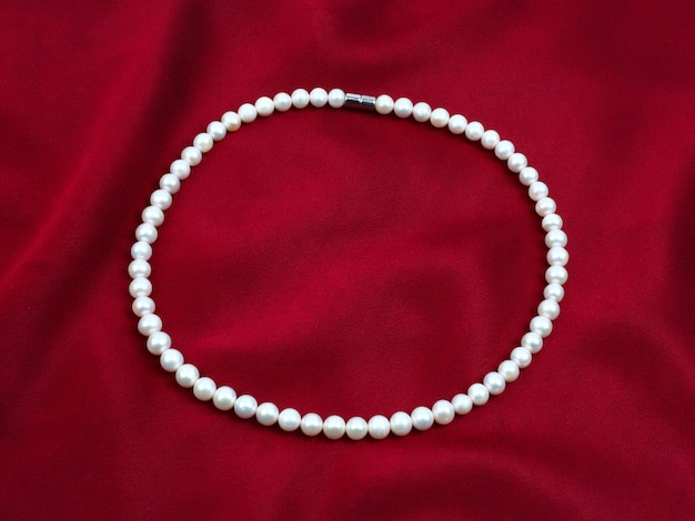 Белое жемчужное ожерелье на красном атласном бархате с текстурой шелка