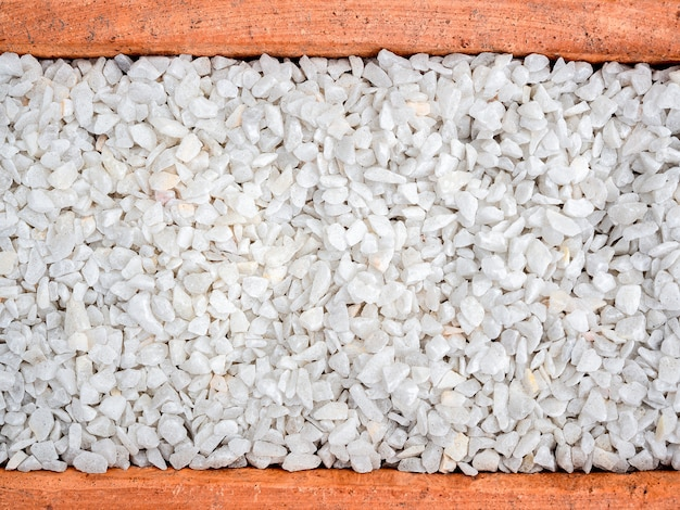 白い小石の背景。テラコッタ鍋、上面の石砂利のテクスチャ。