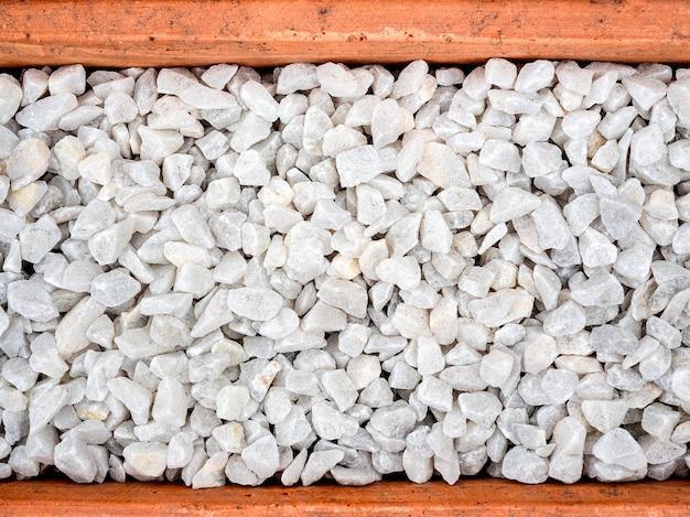 White pebble background. stone gravel texture in terracotta pot, top view.
