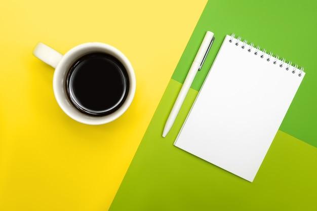 Белая ручка и блокнот, на разноцветном фоне с чашкой кофе.
