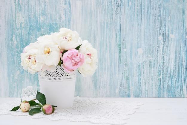 Букет белых пионов в белой вазе на столе, копией пространства.
