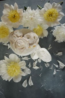 White peonies and vanilla meringue cakes on blue  delicate wedding background top view