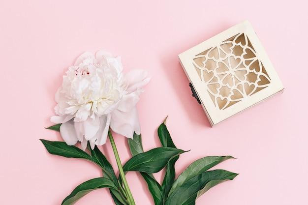 나무 선물 상자와 파스텔 핑크 배경에 흰 모란 꽃