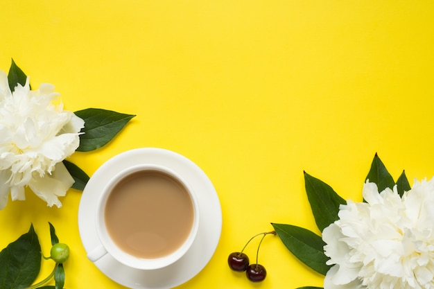 White peony flowers cherry berries cup of coffee on yellow bright background.