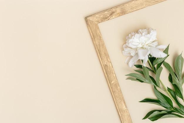 파스텔 베이지색 배너의 복고풍 골든 프레임에 녹색 잎이 있는 흰색 모란