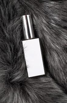 灰色の毛皮の白い香水瓶。