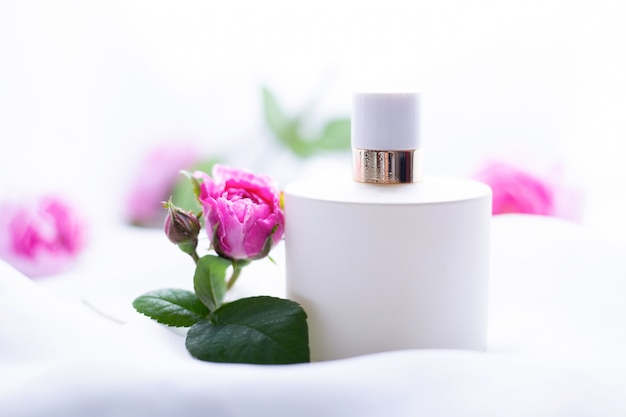 White perfume with flowers on a light background