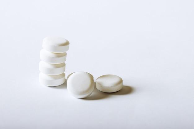 白い背景の上の白い薬局の丸薬。