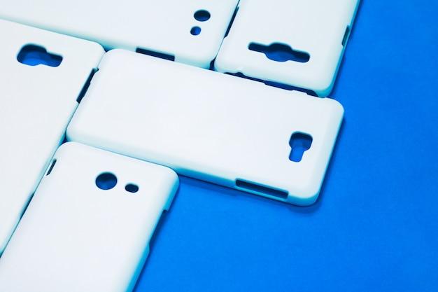 White phone cases on vivid blue background.