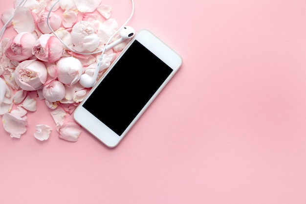 White phone and earphones lie on delicate roses and petals on a pink background