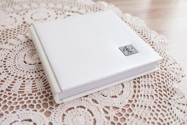 Белая фотокнига в кожаном переплете. стильный свадебный фотоальбом. семейный фотоальбом на столе. красивый блокнот или фотокнига с изящным ажурным тиснением на деревянном столе.