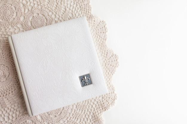 Белая фотокнига в кожаном переплете. стильный свадебный фотоальбом. семейный фотоальбом на белом столе. красивый блокнот или фотокнига с элегантным ажурным тиснением на белом фоне.