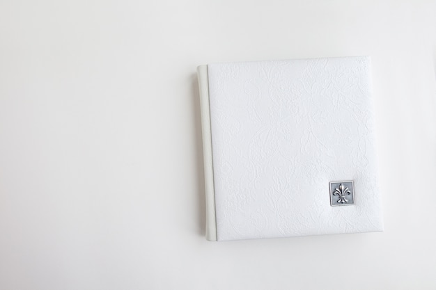 White photo book with leather cover. stylish wedding photo album.  family photoalbum on the white table . beautiful notepad or photobook with elegant openwork embossing on a white background.
