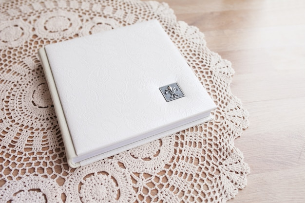 White photo book with leather cover. stylish wedding photo album.  family photoalbum on the white table . beautiful notepad or photobook with elegant openwork embossing on a white table.