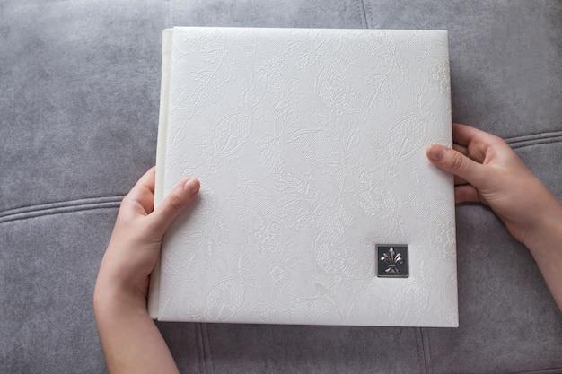 Белая фотокнига в кожаном переплете. руки женщины держа фотокнигу. стильный свадебный или семейный фотоальбом