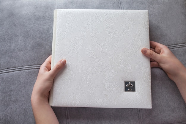 White photo book with leather cover. woman hands holding a photobook. stylish wedding or family photo album