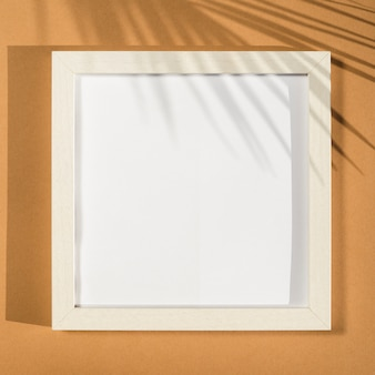 White photo frame on a beige background with a palm leaf shadow