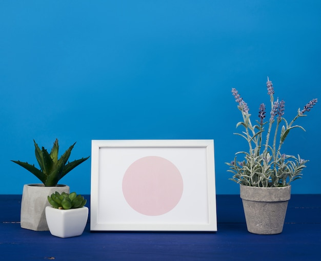 White photo frame and ceramic pot with a growing plant on a blue wooden table