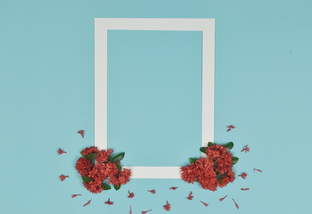 White photo frame decorated with red spike flowers on the side.