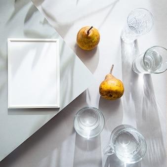 Белые очки в рамке для фотографий с водой и грушами на сером столе