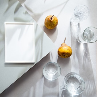 White photo frame glasses with water and pears flat lay on gray table