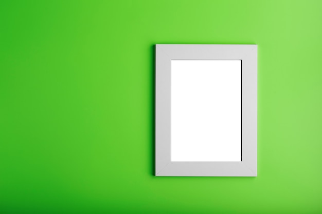 White photo frame on green surface