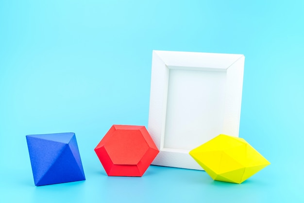 White photo frame(made from paper) and colourful paper jewels on light blue background