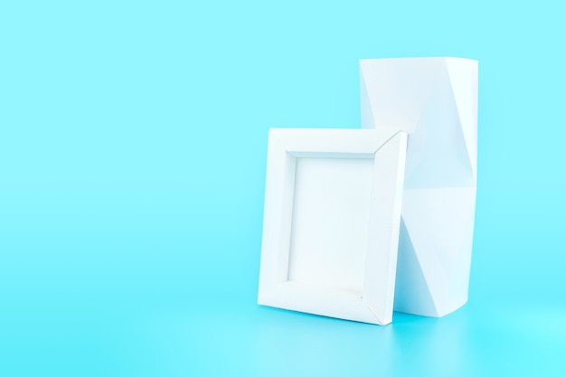 White photo frame(made from paper) and polygon vase on light blue background