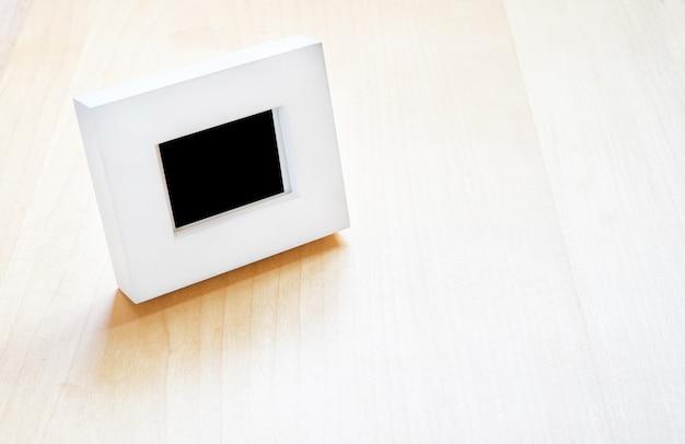 나무 테이블에 흰색 사진 프레임, 템플릿 검은 영역에 사진을 추가하기 위해 모의