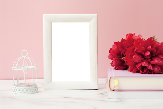 White photo frame on the table next to flowers, books and a candlestick