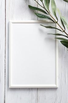 Белая фоторамка с веточкой эвкалипта на белом деревянном столе