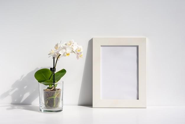 테이블에 투명 냄비에 피는 난초 꽃과 흰색 사진 프레임