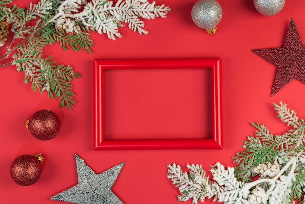 White photo frame with branches and christmas ornaments