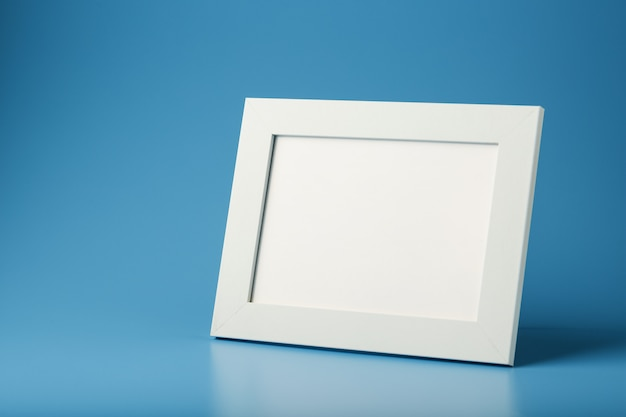 A white photo frame with an empty space on a blue background.