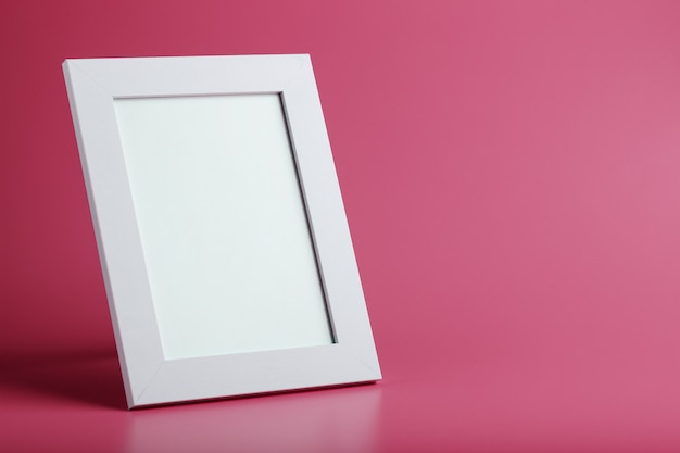 White photo frame with an empty space on a pink background.