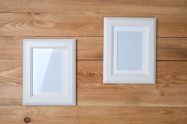 White photo frames on wooden background