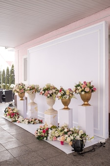 花のある白い写真ゾーン。イベントの装飾。