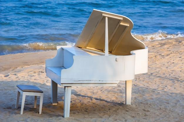 Белое пианино на берегу моря для свадебной фотографии.