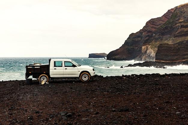 White pickup near the ocean, rocky shore.