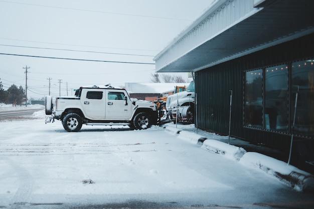 灰色の建物の前に駐車した白いピックアップトラック