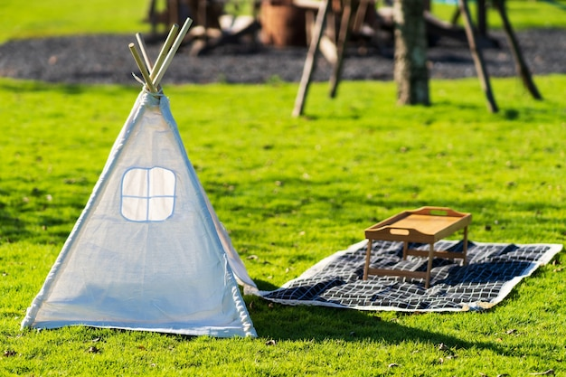 녹색 잔디 배경에 흰색 피크닉 텐트