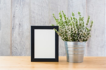 White picture frame and plants in can on wooden desk