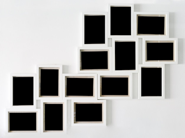 White picture frame and black decorative hanging on white wall