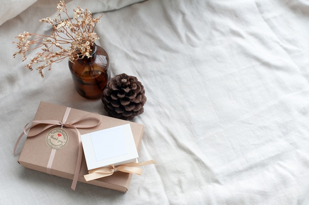 A white picture frame placed in a brown gift box surrounded by a box of small diamond rings tied with cream-colored pine cones dried flowers in a brown glass bottle.