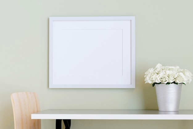 White picture frame on the wall with table and flower in a vase. 3d render.